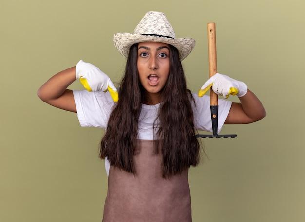 Giovane ragazza del giardiniere in grembiule e cappello estivo che indossa guanti da lavoro tenendo il mini rastrello sorpreso indicando con le dita indice verso il basso in piedi sopra la parete verde