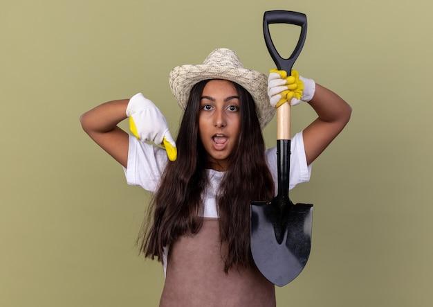 Giovane giardiniere ragazza in grembiule e cappello estivo indossando guanti da lavoro tenendo la pala sorpreso pointign con il dito indice verso il basso in piedi sopra la parete verde