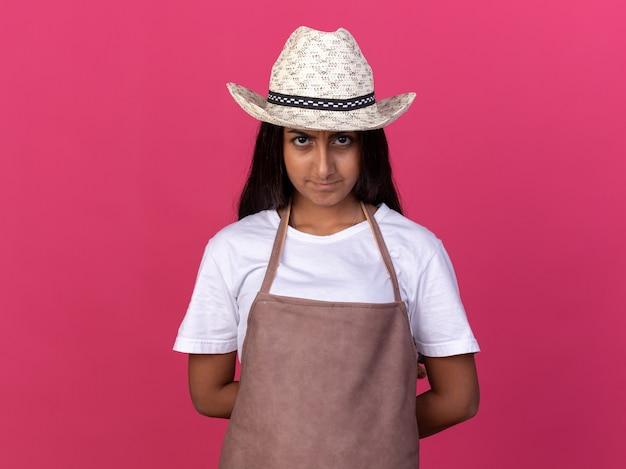 Ragazza giovane giardiniere in grembiule e cappello estivo con faccia seria in piedi sopra il muro rosa