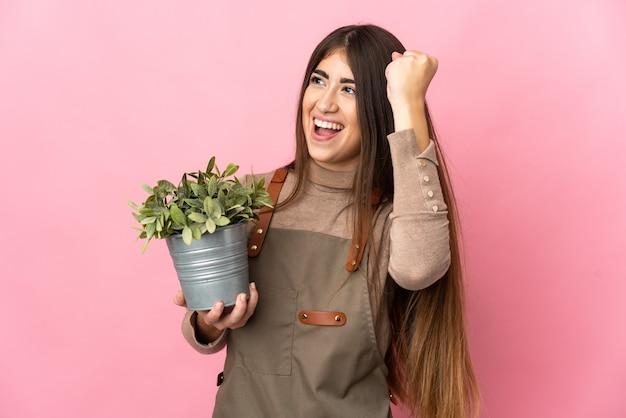 승리를 축하 분홍색 배경에 고립 된 식물을 들고 젊은 정원사 소녀