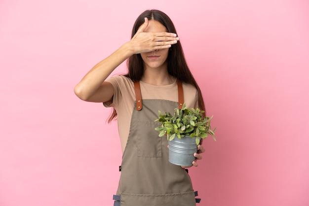 손으로 눈을 덮고 분홍색 배경에 고립 된 식물을 들고 젊은 정원사 소녀. 뭔가보고 싶지 않아