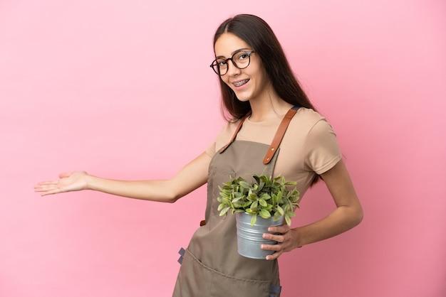 핑크 배경에 고립 된 식물을 들고 젊은 정원사 소녀 올 초대에 손을 옆으로 확장