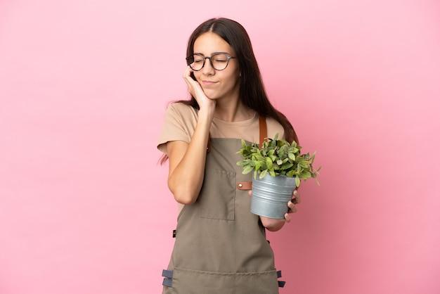 ピンクの背景で隔離の植物を保持している若い庭師の女の子は欲求不満と耳を覆っている