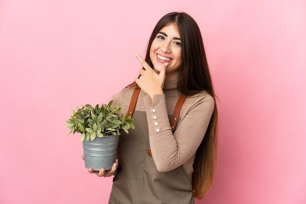 ピンクの背景で隔離の植物を保持している若い庭師の女の子幸せと笑顔