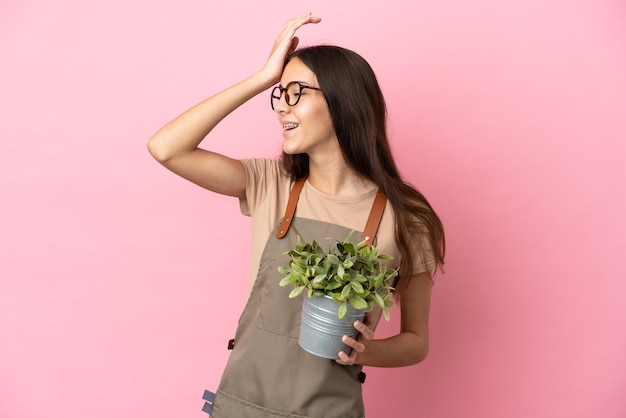 분홍색 배경에 고립 된 식물을 들고 젊은 정원사 소녀는 뭔가를 실현하고 솔루션을 계획하고 있습니다