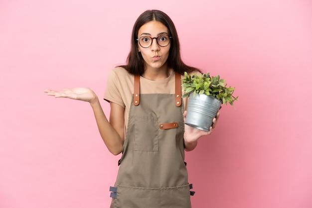 手を上げている間疑いを持っているピンクの背景に分離された植物を保持している若い庭師の女の子