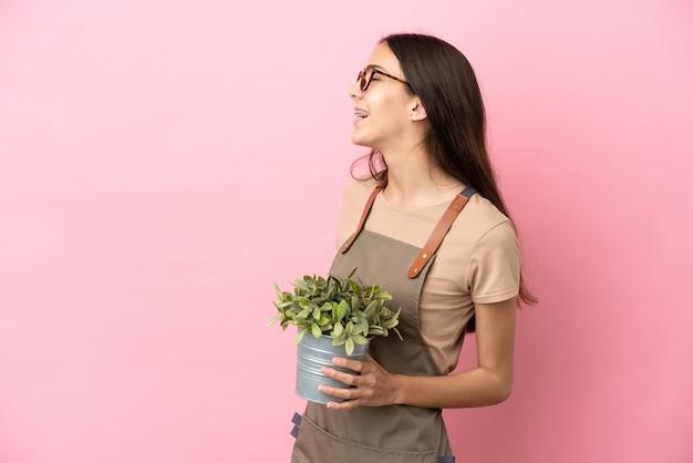 측면 위치에 웃고 분홍색 배경에 고립 된 식물을 들고 젊은 정원사 소녀