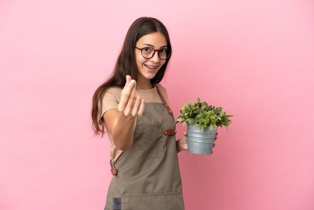 ピンクの背景で隔離の植物を保持している若い庭師の女の子はお金のジェスチャーを作る