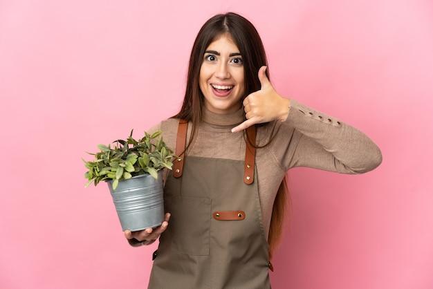 전화 제스처를 만드는 분홍색 배경에 고립 된 식물을 들고 젊은 정원사 소녀. 나에게 다시 전화