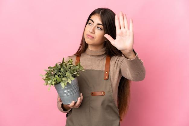 정지 제스처를 만드는 분홍색 배경에 고립 된 식물을 들고 젊은 정원사 소녀 실망
