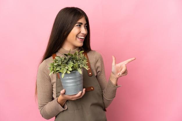 横に指を指して製品を提示するピンクの背景に分離された植物を保持している若い庭師の女の子