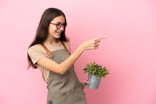 横に指を指して製品を提示するピンクの背景で隔離の植物を保持している若い庭師の女の子