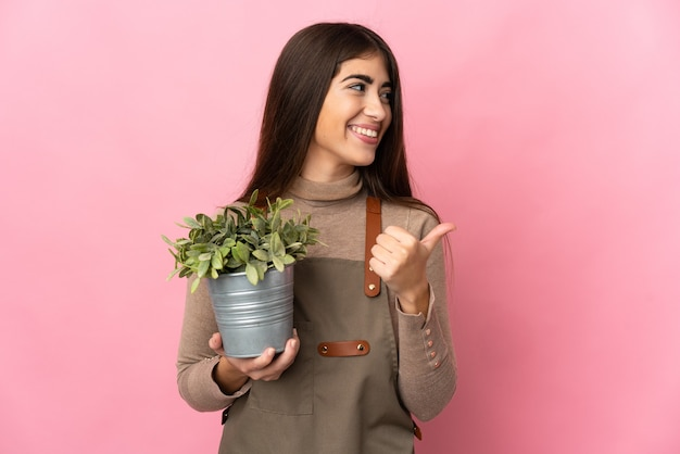 제품을 제시하기 위해 측면을 가리키는 분홍색 배경에 고립 된 식물을 들고 젊은 정원사 소녀