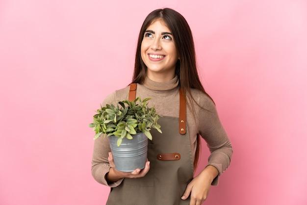 찾는 동안 아이디어를 생각하는 분홍색 배경에 고립 된 식물을 들고 젊은 정원사 소녀