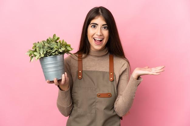 Молодая девушка-садовник держит растение, изолированное на розовом фоне с шокированным выражением лица