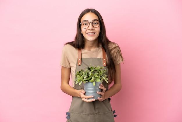 驚きの表情でピンクの背景に分離された植物を保持している若い庭師の女の子