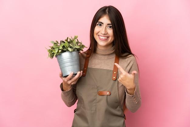 제스처를 엄지 손가락을주는 분홍색 벽에 고립 된 식물을 들고 젊은 정원사 소녀