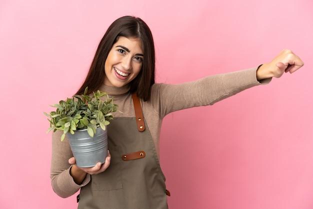 ピンクの壁に隔離された植物を保持している若い庭師の女の子が親指を立てる