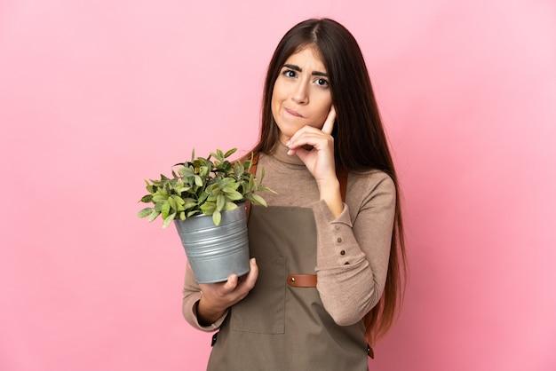 의심과 생각을 갖는 분홍색 벽에 고립 된 식물을 들고 젊은 정원사 소녀