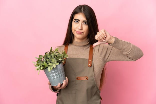 부정적인 표현으로 아래로 엄지 손가락을 보여주는 분홍색 벽에 고립 된 식물을 들고 젊은 정원사 소녀