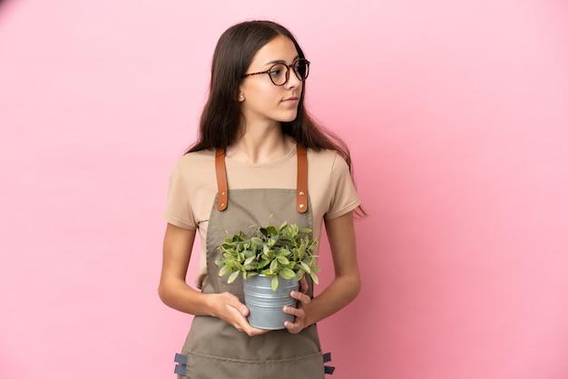 고립 된 식물을 들고 젊은 정원사 소녀