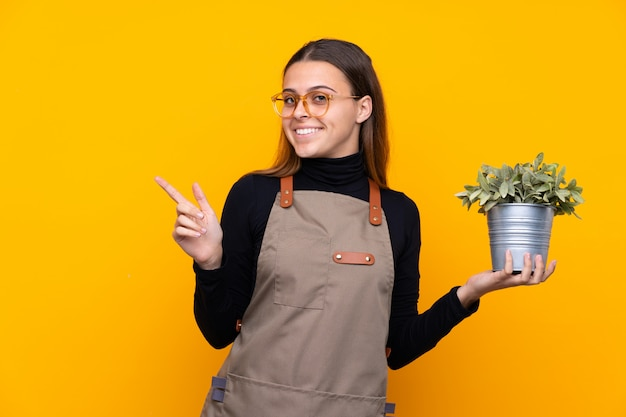 Young gardener girl holding a plant over isolated yellow pointing finger to the side