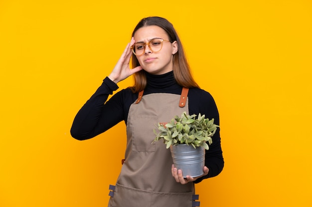 Young gardener girl holding a plant over isolated yellow unhappy and frustrated with something. negative facial expression