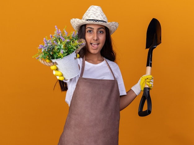 オレンジ色の壁の上に元気に立って笑顔の鉢植えとシャベルを保持している若い庭師の女の子