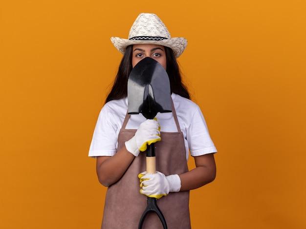 オレンジ色の壁の上に立っている深刻な顔で彼女の顔の前にシャベルを保持している若い庭師の女の子