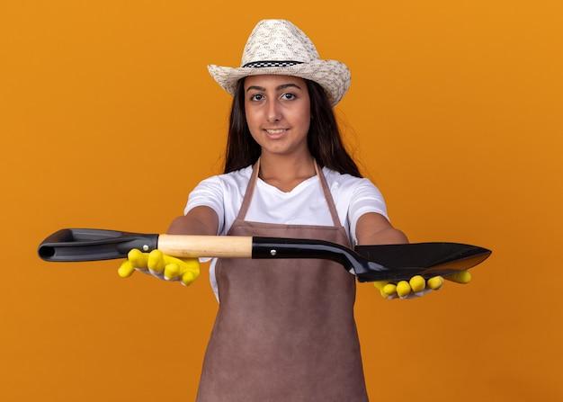 オレンジ色の壁の上に立っている顔に笑顔でシャベルを保持している若い庭師の女の子