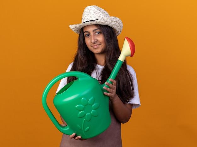 オレンジ色の壁の上に立っている顔に笑顔でじょうろを保持している若い庭師の女の子