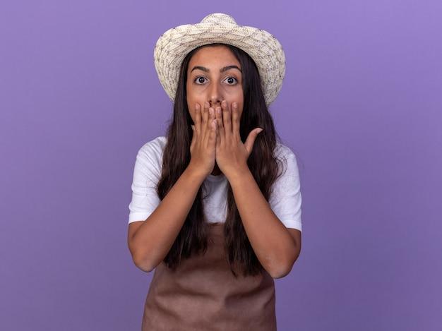 앞치마와 여름 모자에있는 젊은 정원사 소녀는 보라색 벽 위에 서있는 손으로 입을 덮고 놀랐고 충격을 받았습니다.