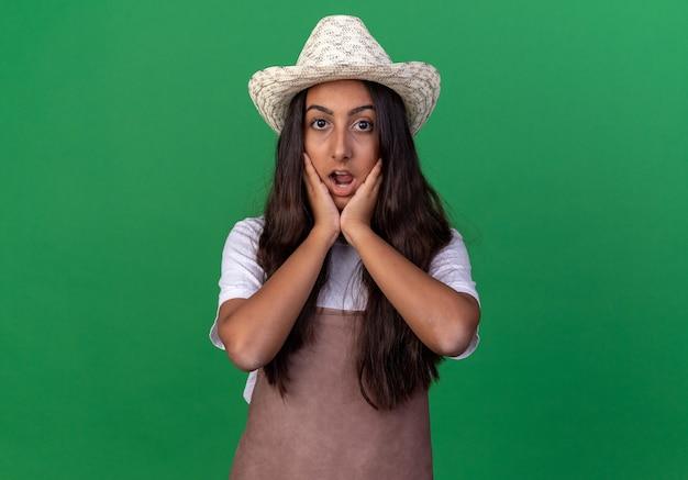 앞치마와 여름 모자에있는 젊은 정원사 소녀는 놀랍고 녹색 벽 위에 서있는 그녀의 뺨에 손으로 놀랐습니다.
