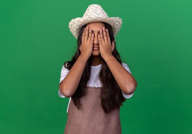 緑の壁の上に立っている手で目を閉じるエプロンと夏の帽子の若い庭師の女の子
