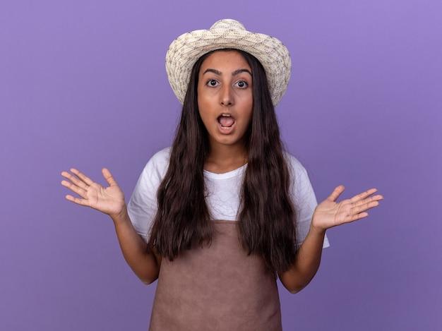 エプロンと夏の帽子の若い庭師の女の子は、紫色の壁の上に立って混乱し、不確かな腕を上げる