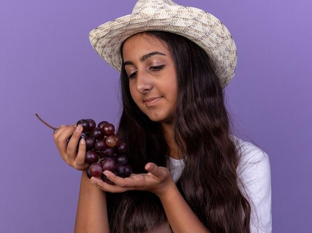 エプロンと夏の帽子の若い庭師の女の子は、紫色の壁の上に立って愛を込めてそれを見ているブドウの束を保持しています