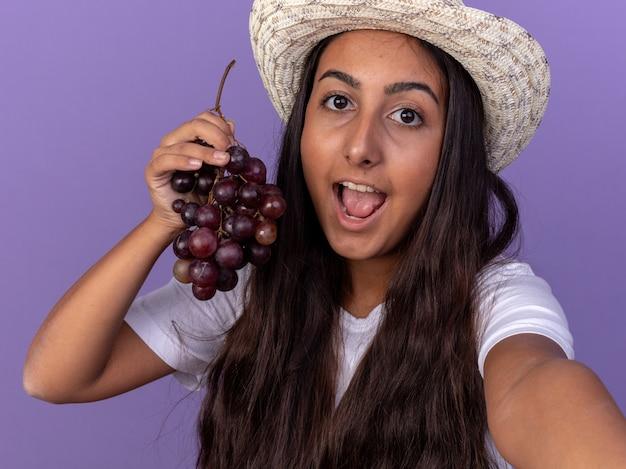 보라색 벽 위에 서 행복 한 얼굴로 웃 고 포도의 무리를 들고 앞치마와 여름 모자에 젊은 정원사 소녀