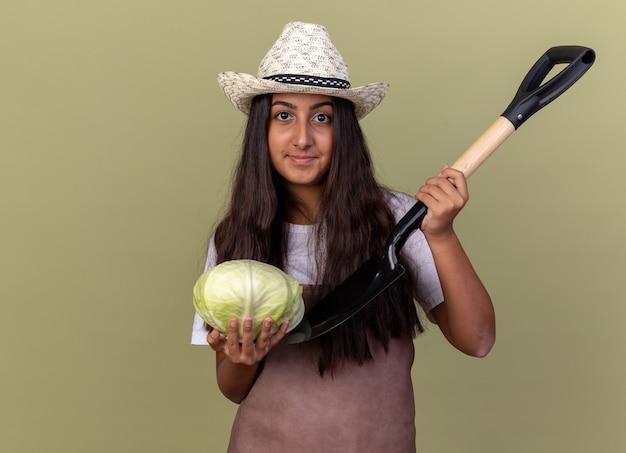 緑の壁の上に立っている顔に笑顔でキャベツとシャベルを保持しているエプロンと夏の帽子の若い庭師の女の子