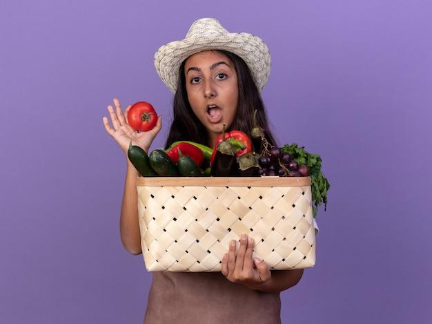 Молодая девушка-садовник в фартуке и летней шляпе держит ящик, полный овощей и свежих помидоров, счастливая и удивленная, стоя у фиолетовой стены