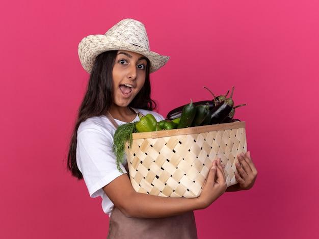 エプロンと夏の帽子の若い庭師の女の子は、ピンクの壁の上に元気に立って幸せで興奮した笑顔の野菜でいっぱいの木枠を保持しています