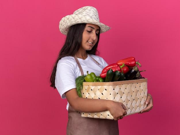 ピンクの壁の上に立って自信を持って笑顔に見える野菜でいっぱいの木枠を保持しているエプロンと夏の帽子の若い庭師の女の子
