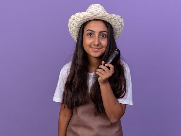 가지를 들고 앞치마와 여름 모자에 젊은 정원사 소녀 보라색 벽 위에 서 행복하고 긍정적 인 미소