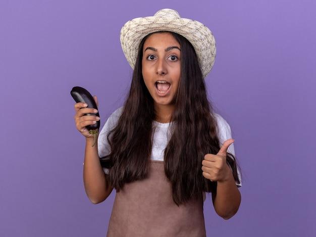 가지를 들고 앞치마와 여름 모자에 젊은 정원사 소녀 보라색 벽 위에 서있는 엄지 손가락을 보여주는 행복하고 놀란