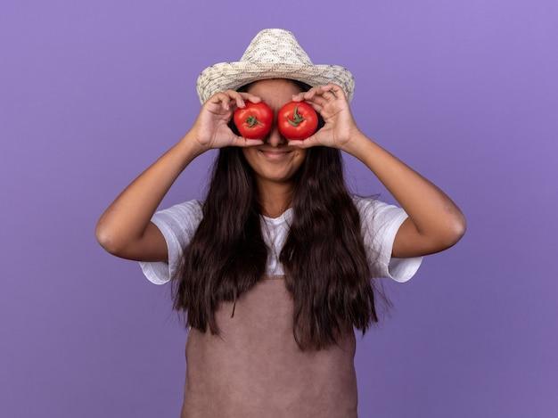 エプロンと夏の帽子の若い庭師の女の子は、紫色の壁の上に立っている幸せそうな顔で笑顔で目を覆っている新鮮なトマトを保持しています
