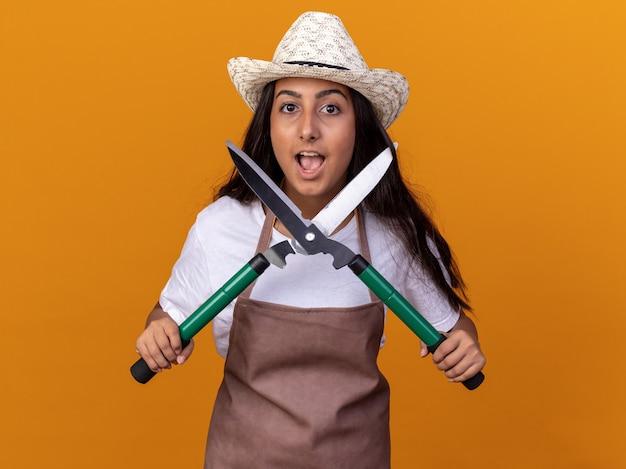 オレンジ色の壁の上に立って幸せで驚いたヘッジクリッパーを保持しているエプロンと夏の帽子の若い庭師の女の子