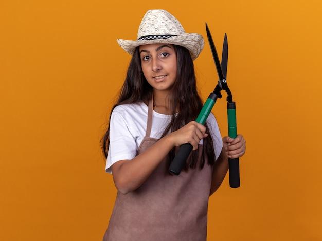 オレンジ色の壁の上に立って自信を持って笑っているヘッジクリッパーを保持しているエプロンと夏の帽子の若い庭師の女の子