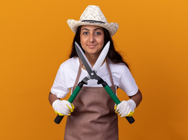 オレンジ色の壁の上に立っている顔に笑顔でヘッジクリッパーを保持しているエプロンと夏の帽子の若い庭師の女の子
