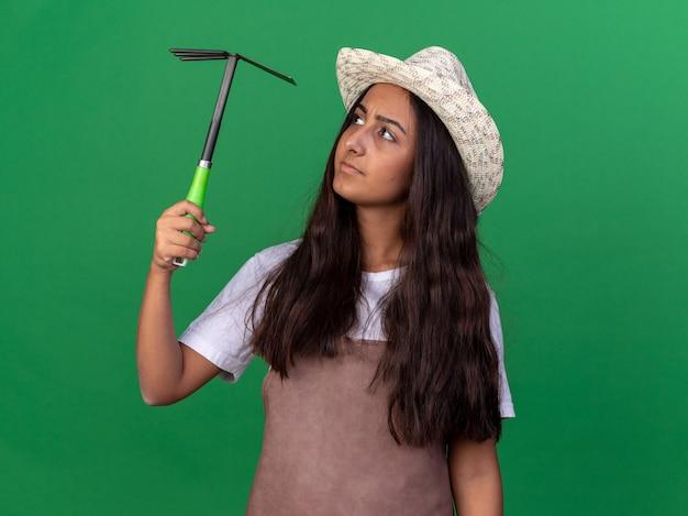 エプロンと夏の帽子をかぶった若い庭師の女の子は、緑の壁の上に立って興味をそそられてそれを見てマットックを保持しています