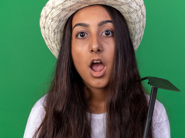 緑の壁の上に立って驚いたマトックを保持しているエプロンと夏の帽子の若い庭師の女の子