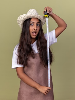 エプロンと夏の帽子の若い庭師の女の子は、緑の壁の上に立って幸せで驚きのメジャーテープを保持しています